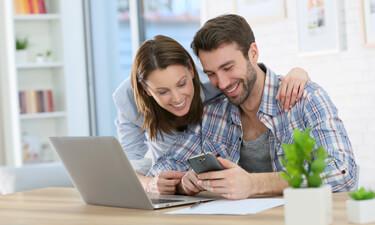 Paar zuhause mit Laptop und Smartphone